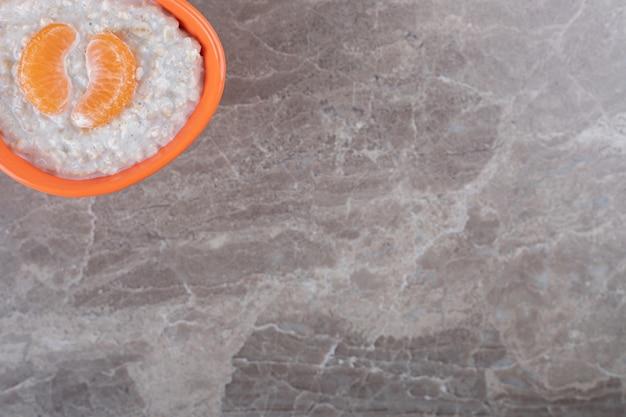 Pomarańczowe plasterki na wierzchu owsianki w misce, na marmurowej powierzchni