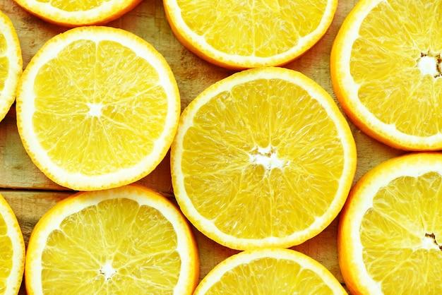 Pomarańczowe plastry tekstury tła, świeże pomarańczowe owoce pomarańczowy wzór na podłoże drewniane - widok z góry