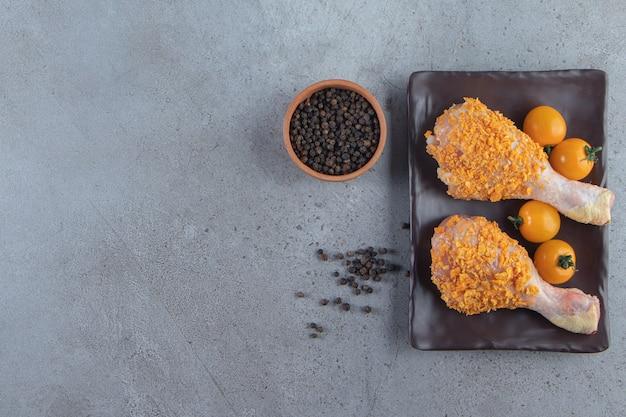 Pomarańczowe pomidory i podudzia z kurczaka na talerzu obok miski przypraw, na tle marmuru.