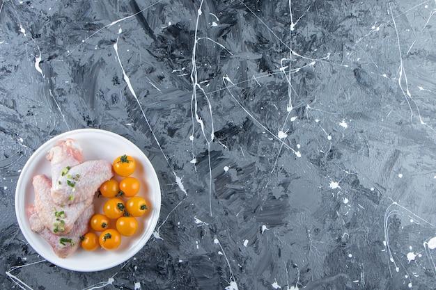 Pomarańczowe pomidory i skrzydełka kurczaka na talerzu, na marmurowym tle.