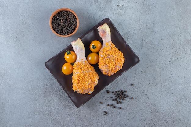 Pomarańczowe pomidory i udka z kurczaka na półmisku obok miski na przyprawy, na marmurowym tle.