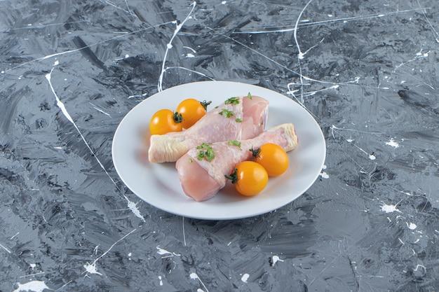 Pomarańczowe pomidory i udka z kurczaka na talerzu, na marmurowej powierzchni.