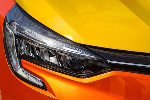 Pomarańczowe reflektory samochodowe. detale zewnętrzne. zbliżenie na jeden z nowoczesnych samochodów z reflektorami led.