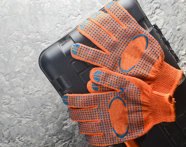 Pomarańczowe rękawice robocze na skrzynce narzędziowej. widok z góry.