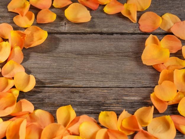 Pomarańczowe róże płatki na drewnianym stole