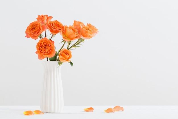 Pomarańczowe róże w białym wazonie na białej powierzchni