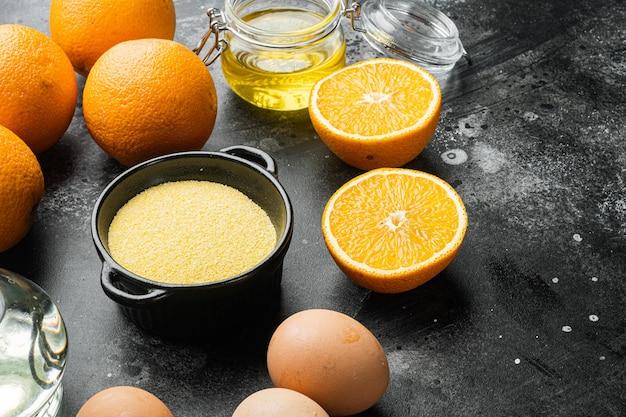 Pomarańczowe składniki ciasta z polenty, z jajkami i zestawem miodu, na czarnym ciemnym tle kamiennego stołu
