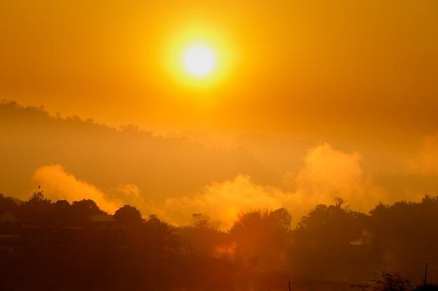 Pomarańczowe słońce aż do wschodu słońca nad górą i odbija się na rzece z porannym dymem mgły.
