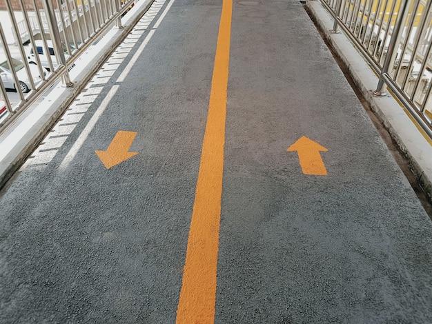 Pomarańczowe strzałki ruchu do przodu i do tyłu z długą linią podziału na podłodze wiaduktu