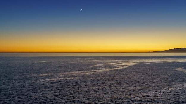 Pomarańczowe światło zachodu słońca po tym, jak słońce znika za horyzontem morza. hiszpania, europa.