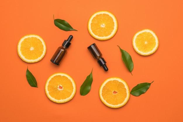 Pomarańczowe tło z plastrami pomarańczy, zielonymi liśćmi i butelkami z pipetami.