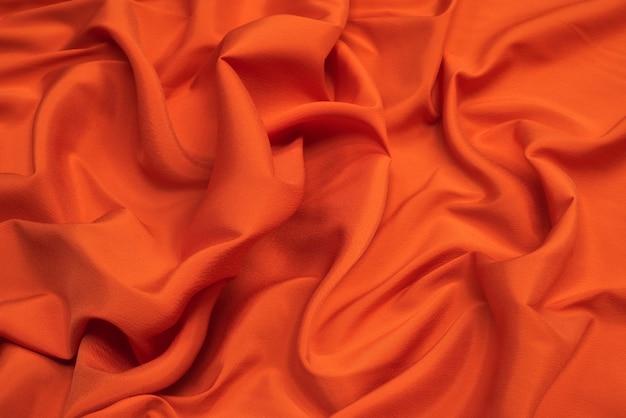 Pomarańczowe tło z tkaniny podszewkowej. zbliżenie tła zmiętej tkaniny.