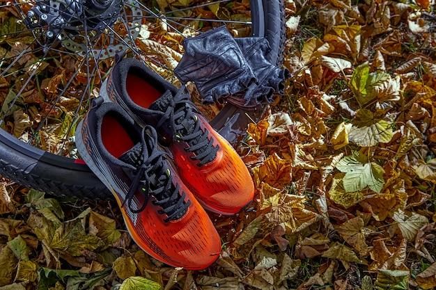 Pomarańczowe trampki, rękawiczki i koło rowerowe w słońcu na tle opadłych jesiennych liści