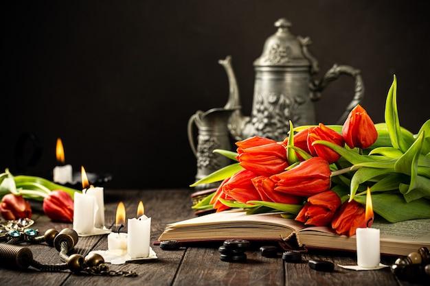 Pomarańczowe tulipany na starej książce z płonącymi świecami z sylwetką w dymie. urodziny, dzień matki pozdrowienie koncepcja z miejsca na kopię