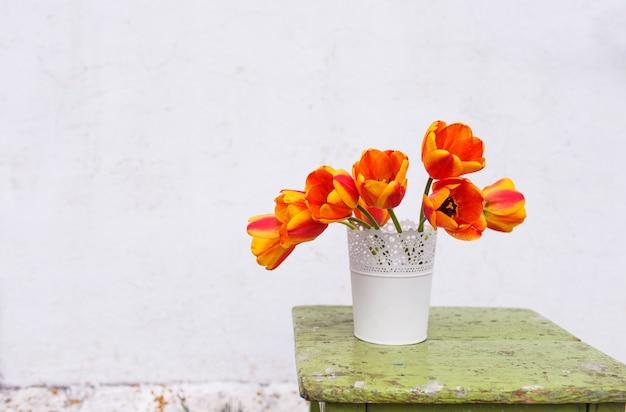 Pomarańczowe tulipany w wazonie na stole na białej ścianie