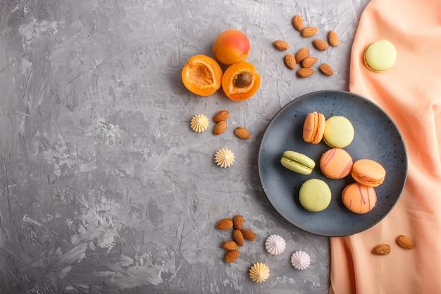 Pomarańczowi i zieleni macarons lub macaroons zasychają na błękitnym ceramicznym talerzu na popielatym betonowym tle, odgórny widok.