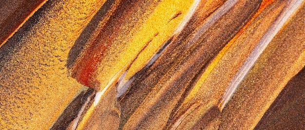 Pomarańczowo-brązowe tło z błyszczącymi rozmazami. streszczenie tekstura farby. kreatywne pociągnięcia pędzlem złotą farbą. koncepcja makijażu. świąteczne tło
