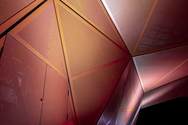 Pomarańczowo-czerwona geometryczna metaliczna konstrukcja z trójkątnych części. architektura nowoczesna. streszczenie tło w ciemności.