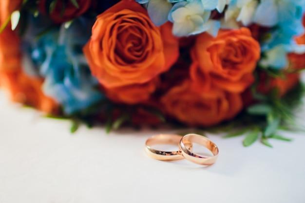 Pomarańczowo-niebieska kompozycja kwiatowa na wesele: pomarańczowe róże i niebieska ostróżka.
