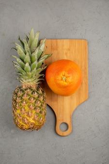 Pomarańczowy ananasowy świeży łagodny dojrzały na drewnianym brown biurku