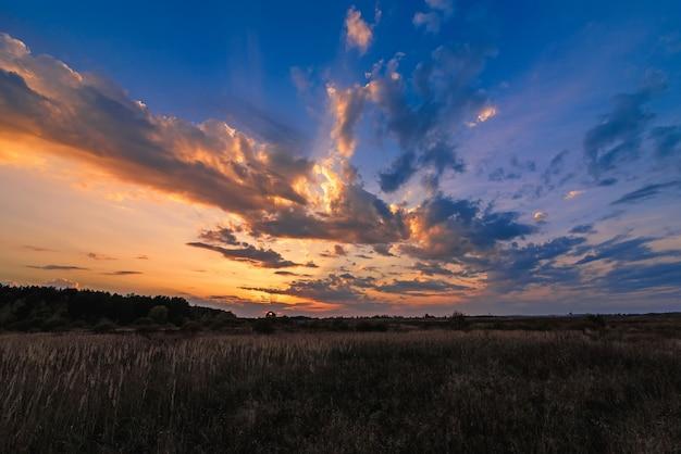 Pomarańczowy błękitny zmierzch z słońce promieniami przez chmur w niebie w polu w wieczór