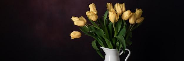 Pomarańczowy bukiet tulipanów w białym dzbanku na ciemnym tle