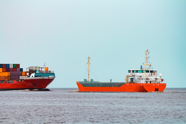 Pomarańczowy bulker mija czerwony kontenerowiec na morzu bałtyckim