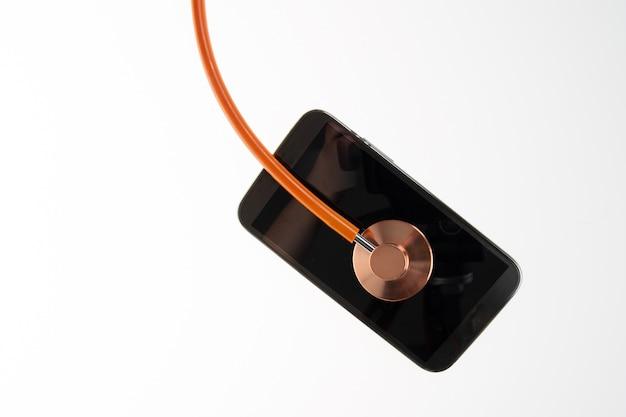 Pomarańczowy cienki stetoskop z telefonem komórkowym