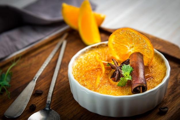 Pomarańczowy creme brulee deser w białym pucharze z cynamonem i mennicą na drewnianym tle