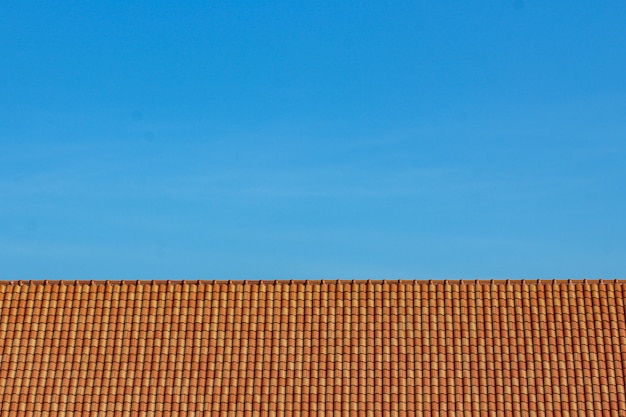 Pomarańczowy dachowej płytki i niebieskiego nieba tło