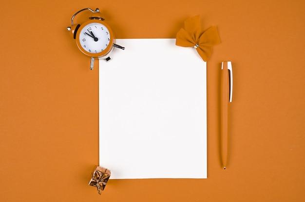 Pomarańczowy długopis z papierem na tle bożego narodzenia.