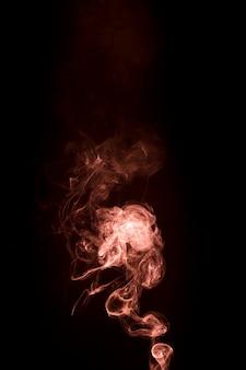 Pomarańczowy dym rośnie na czarnym tle