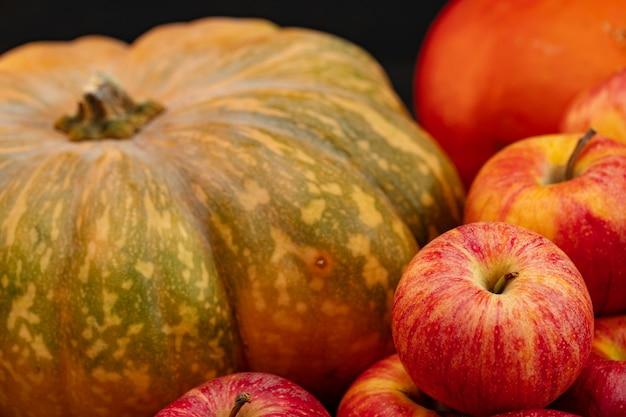 Pomarańczowy dyni i stos czerwonych jabłek z bliska
