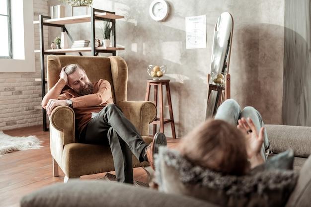 Pomarańczowy golf. prywatny terapeuta w pomarańczowym golfie rozmawia z klientem leżącym na kanapie obok niego