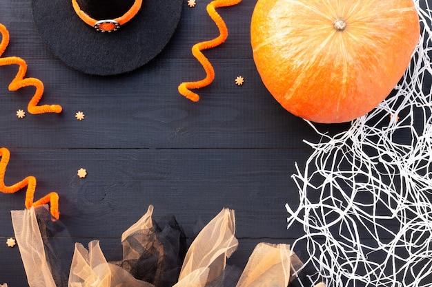 Pomarańczowy i czarny flatlay na halloween. dynia, tiul, pajęczyna na czarnym tle drewna. skopiuj miejsce