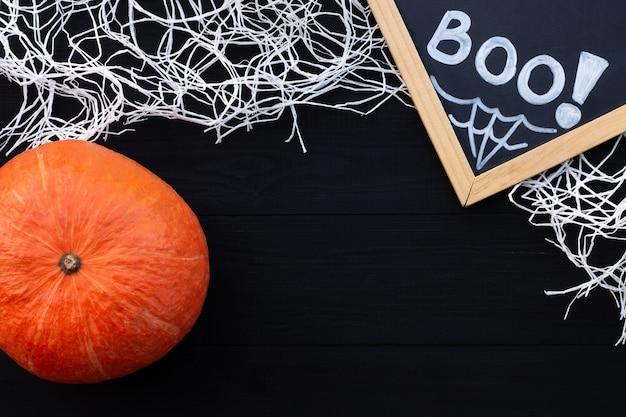 Pomarańczowy i czarny flatlay na halloween. kreda napis boo, dynia i pajęczyna na czarnym tle drewnianych. skopiuj miejsce
