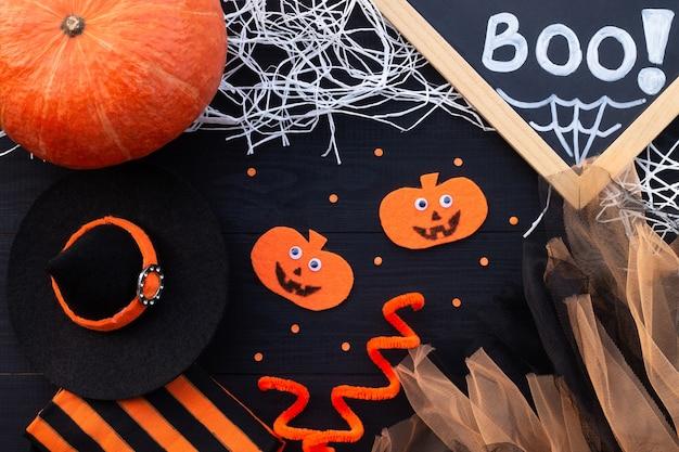 Pomarańczowy i czarny flatlay na halloween. kreda napis boo, dynie z filcu, tiulu, pajęczyna na czarnym tle drewnianych.