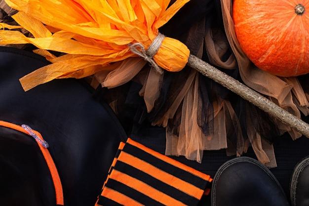 Pomarańczowy i czarny flatlay na halloween. ubrania czarownicy: pończochy, buty, czapka, miotła, spódnica na czarnym tle
