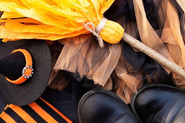 Pomarańczowy i czarny flatlay na halloween. ubrania czarownicy: pończochy, buty, czapka, miotła, spódnica