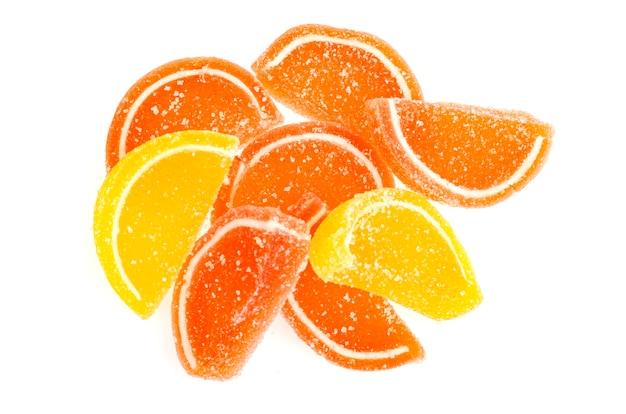 Pomarańczowy i żółty plastry marmolady słodkich owoców w cukrze na białym tle