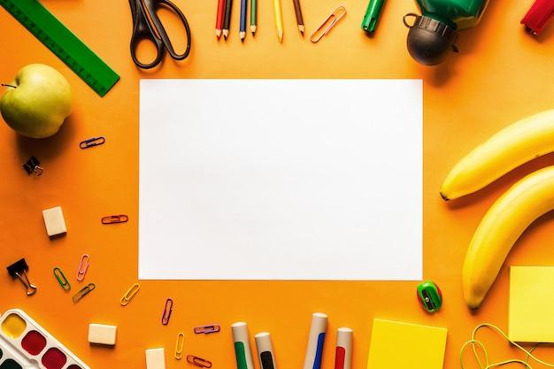 Pomarańczowy jasny stół biurkowy z akcesoriami szkolnymi i artykułami biurowymi
