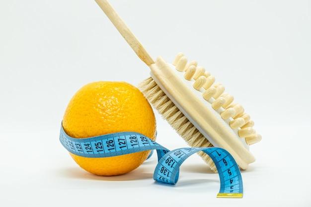 Pomarańczowy jest owinięty niebieską taśmą pomiarową, dwustronna okrągła szczotka do masażu do szczotkowania ciała