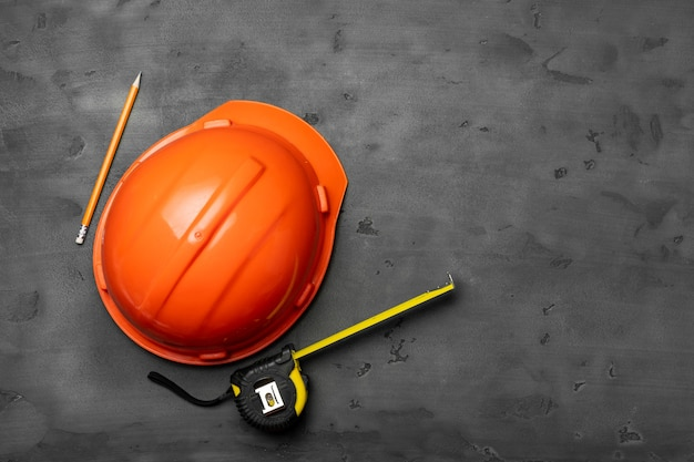 Pomarańczowy kask, linijka i ołówek na czarnym widoku z góry