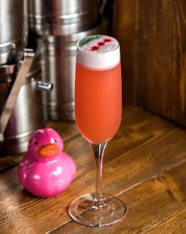 Pomarańczowy koktajl w kieliszku szampana przyozdobionym zielenią i czerwienią błyszczy