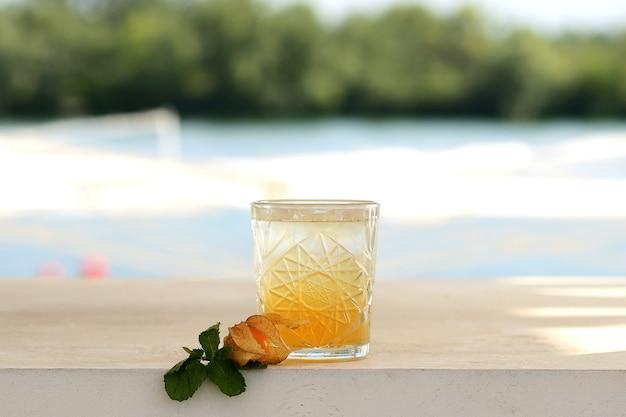 Pomarańczowy koktajl w szklance. z kwiatowym wystrojem