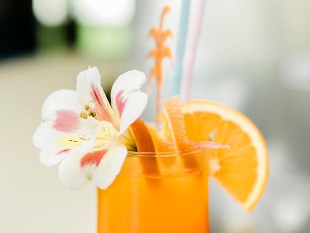 Pomarańczowy koktajl z owocami ozdobionymi orchideą