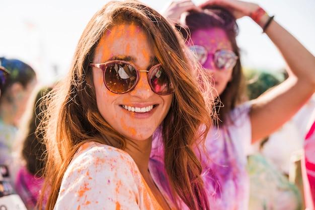 Pomarańczowy kolor holi na twarzy kobiety w okularach przeciwsłonecznych