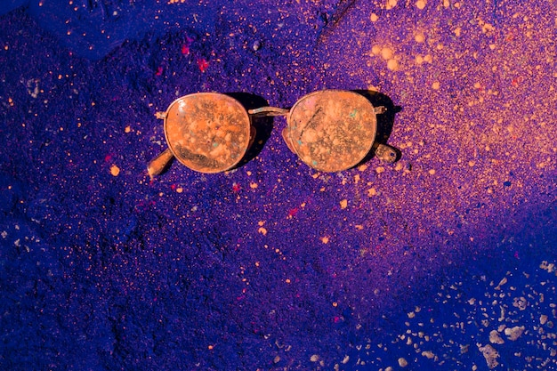 Pomarańczowy kolor holi nad okularami przeciwsłonecznymi na niebieskim proszku