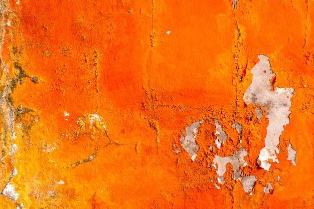 Pomarańczowy kolor malowany na betonowej ścianie łuszczy się. stary i brudny ścienny tekstury tło