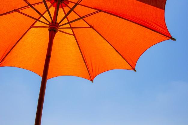 Pomarańczowy kolor plażowy parasol robić drewniany dla ochraniającego światła słonecznego z jaskrawym niebieskiego nieba tłem.